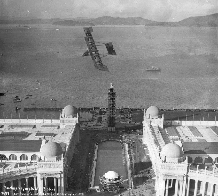 "Aviator Lincoln Beachey performing in his biplane over the fairgrounds in 1913, before the official opening. Beachey was later killed during an air show at the PPIE when his plane crashed into the San Francisco Bay. Via the <a href=""http://www.flysfo.com/museum/exhibitions/fancy-flying"">SFO Museum</a>."