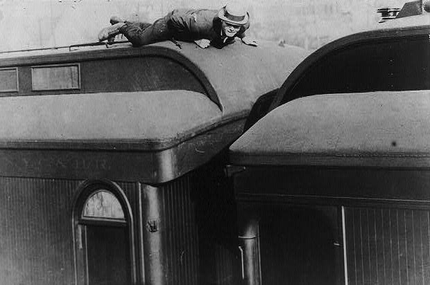 """A man lying prone atop a railroad passenger car in a 1907 photo titled, """"Tramp life—how Jack London traveled on a passenger coach."""" (From the Bain Collection, Library of Congress)"""