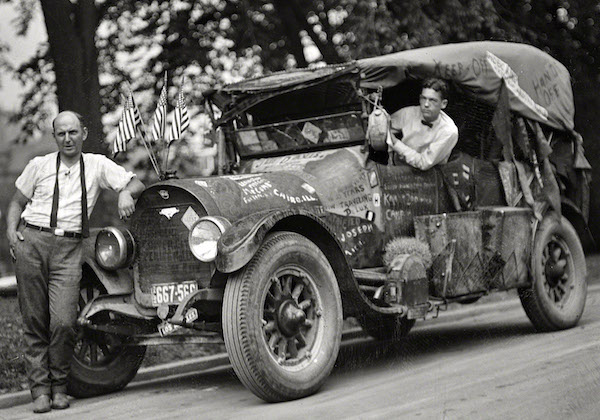 """Jeff Davis, left, and his """"rubber tramp"""" car with graffiti, including """"Davis,"""" """"Keep Off,"""" """"Hobo King,"""" """"Hands Off,"""" and """"Traveling DeLux,"""" in 1924. (From the Harris & Ewing Collection, Library of Congress)"""