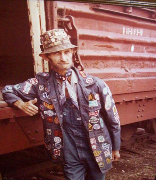 A photo of a 20th-century hobo in a denim jacket covered in patches. (Via the Hobo Museum)