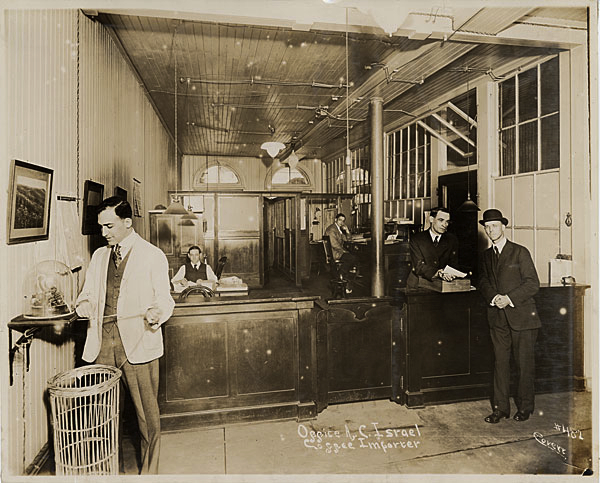 "In 1917, coffee importer A.C. Israel of New Orleans had a ticker that spat out the latest coffee prices. The ticker's overflow was captured in a tall wicker waste paper basket. Photo via <a href=""http://www.officemuseum.com/photo_gallery_1910s%20ii.htm"">Early Office Museum</a>."