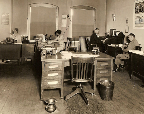 Typical floor companions in offices of the 1920s were waste baskets and spittoons, as seen in this photograph taken in 1929. Photo via Early Office Museum.