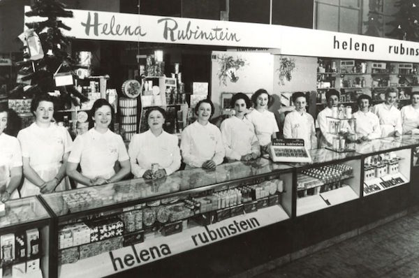 Saleswomen in uniforms line a Helena Rubinstein makeup counter. (© Helena Rubinstein, Inc.)