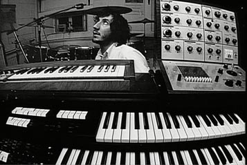 Top: Keith Emerson performing live on his Moog modular synthesizer. Via Keith Emerson's Facebook page. Above: Pete Townshend in his home studio, with an EMS VCS 3 (at right) sitting atop his Lowrey organ. Via Archive.org.