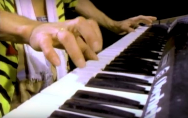 "Eddie Van Halen, playing the Oberheim synthesizer part on the video for ""Jump."""