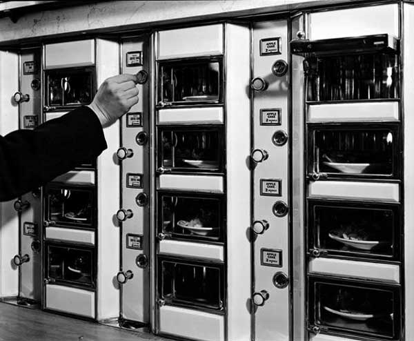 """A customer makes his selection in this 1936 photo by Berenice Abbott. Via the <a href=""""http://digitalcollections.nypl.org/collections/robert-f-byrnes-collection-of-automat-memorabilia#/?tab=navigation"""">New York Public Library</a>."""