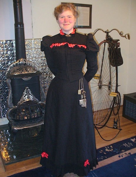 Sarah wears a chatelaine, a piece of Victorian jewelry that holds useful objects like a pencil and notebook, a coin purse, or sewing tools. Behind her is the 1890s gas parlor heater the Chrismans installed in their house, which was built in 1888. (From ThisVictorianLife.com)
