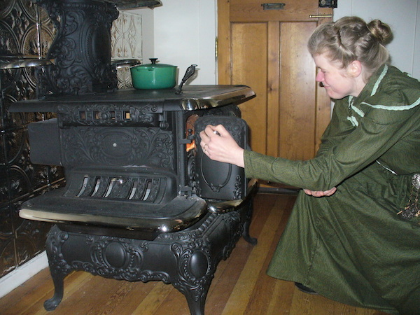 The Chrismans replaced their home's 1980s electric oven with an 1890s cast-iron wood-burning stove, the Charm Crawford Royal. Sarah lights the wood with a long match kept in an antique matchsafe screwed to the wall. (From ThisVictorianLife.com)