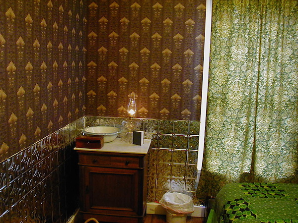 "In the Victorian era, the Chrismans' home would have had wallpaper in every room. They've only been able to paper one room so far; the pattern, ""Imperial Artichoke,"" is a replica of an 1893 wallpaper pattern. (From ThisVictorianLife.com)"