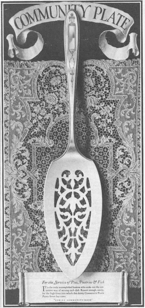 "A Community Plate ad introducing a utensil ""for the service of pies, pastries, and fish"" in the ""Grosvenor"" pattern places the silverware on an intricate lace background. Click on the image to see it larger. (Via Nancy Eleanor Gluck's ""Silver Threads"" blog)"