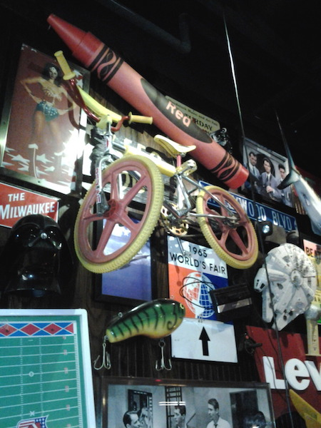 "At a Friday's in the 2010s, a BMX bicycle hangs among pop culture memorabilia referencing ""Ghostbusters,"" ""Star Wars,"" Wonder Woman, and the 1965 World's Fair. (Via BMX Museum Forum)"