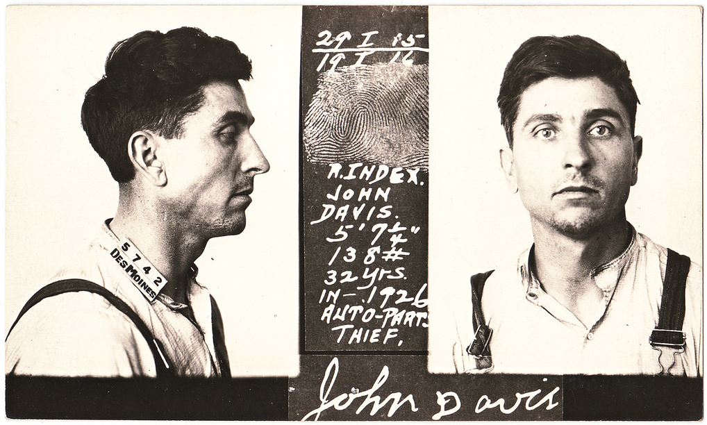 Fingerprints eventually replaced the detailed measurement list, as seen on this mugshot of John Davis from 1926.