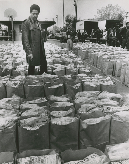 "Black Panther leader Bobby Seale inspects bags of groceries the organization has prepared to hand out to impoverished families in Oakland, on March 31, 1972. Photo by Howard Erker. (Courtesy of the Oakland Museum of California, the ""Oakland Tribune"" collection)"
