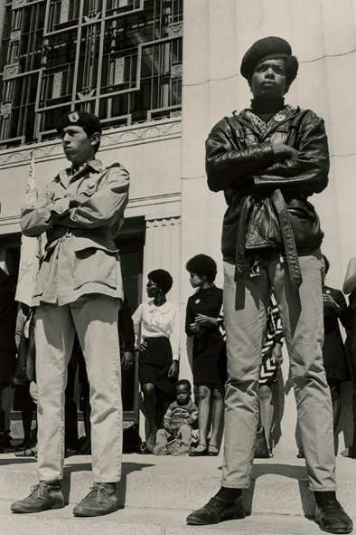 "Black Panthers stand in front of the Alameda County Court House on July 14, 1968, the first day of Huey Newton's murder trial. The men in front wear typical Panther-style jackets and berets. In the background, the women sport natural hairdos and slinky Mod skirts. Photo by Lonnie Wilson. (Courtesy of the Oakland Museum of California, the ""Oakland Tribune"" Collection)"