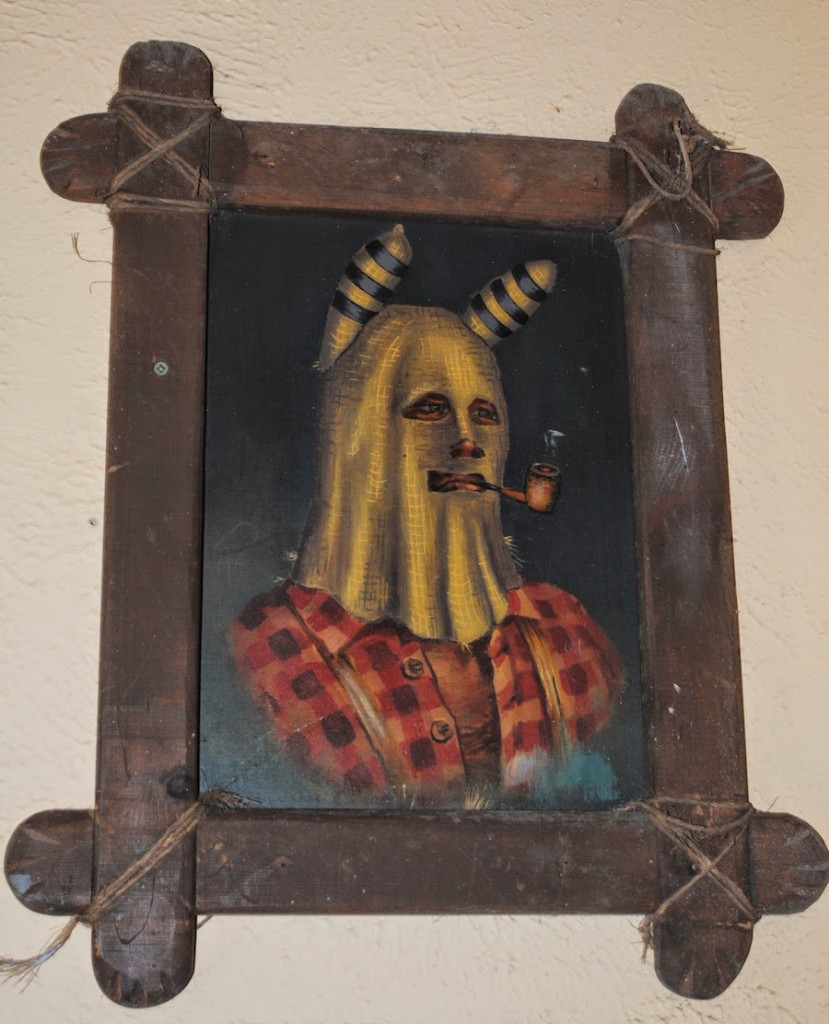 "In the waiting area for Fire in the Hole, you see portraits of ""Baldknobbers"" like this one. The theme park is in Stone County, which never had a Bald Knobber organization. Only one of  the three groups wore horned masks, which were black. (Courtesy of The Carpetbagger)"