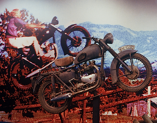 "A 2006 exhibition at the Peterson Automotive Museum in Los Angeles featured a blowup of the famous motorcycle jump by Bud Ekins in ""The Great Escape,"" paired with a facsimile of the actual Triumph used in the movie. Ekins sold the original to a stuntman, and its whereabouts remain unknown."
