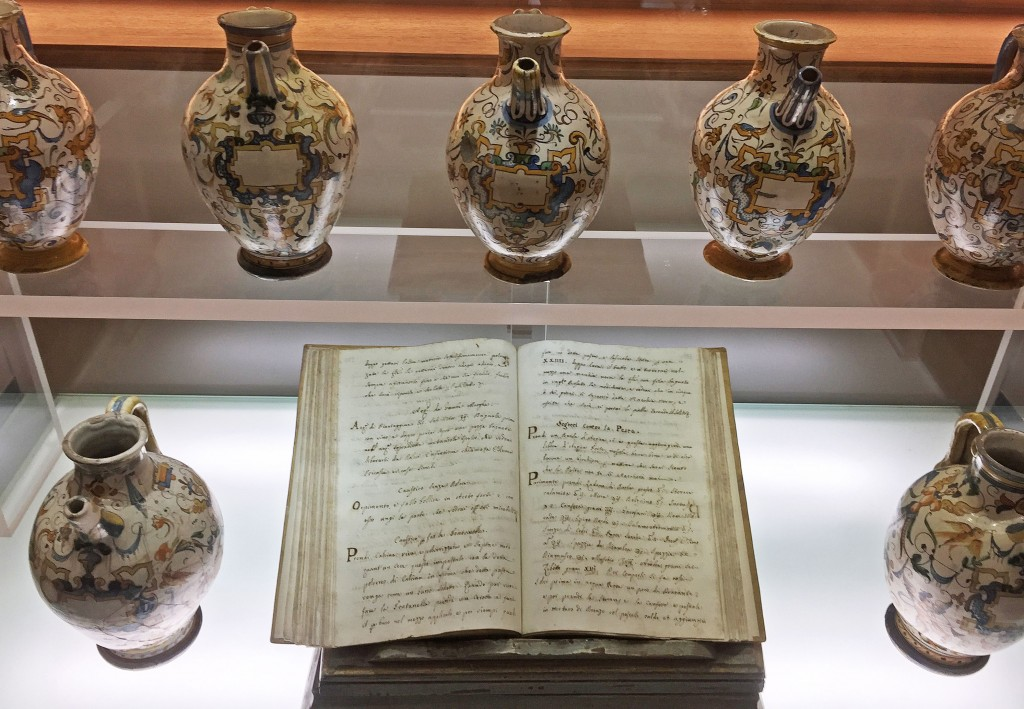 """Original texts and ceramic vessels used by the friars are housed in the shop's museum. The heading on the righthand page reads """"S<em>egreti Contro la Peste</em>"""" or """"Secrets Against the Plague."""""""