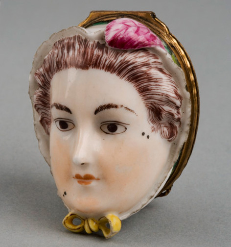 A patch box in the shape of a fashionable woman's face, replete with her own beauty marks. Via the Victoria & Albert Museum