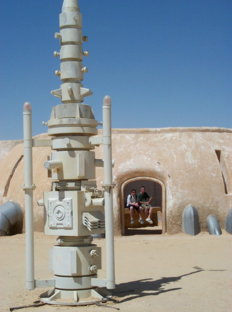 """Alinger and his younger brother sat in Watto's parts shop (made of wood and plaster) on the set of Mos Espa near Tozeur, Tunisia, in 2001, just a few months after the second prequel finished filming there. In the foreground is a moisture-vaporator prop (made of wood) that, in the movie, was used to supply water to the desert planet. This set, a popular tourist site seen in """"The Phantom Menace"""" (1999) and """"Attack of the Clones"""" (2002), is now threatened by sand dunes. (Courtesy of Brandon Alinger)"""