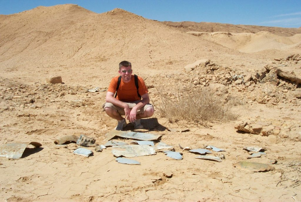 """In 2001, Alinger posed with the fiberglass fragments of the Nazi Flying Wing plane seen in """"Raiders of the Lost Ark."""" This location near Tozeur, Tunisia, represented an archaeological dig in Tanis, Egypt, in the 1981 movie. (Via Prop Store blog)"""